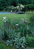 Blick vom Staudenbeet mit Lychnis coronaria (Vexiernelke), Stachys byzantina (Wollziest), Agastache anisata (Duftnessel) und Gräsern über Rasenfläche mit Trittsteinen auf Pool-Area mit Rosen-Pergola und Liegen