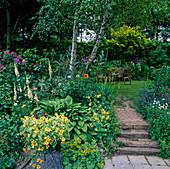 Üppig bepflanzter Garten mit kleiner Treppe und Sitzgruppe