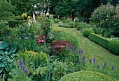 Reich bepflanzter Garten im Sommer, im Hintergrund Gartenhäuschen