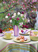 Gedeckter Tisch mit Strauß aus Schachbrettblumen