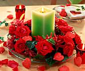 Grüne Kerze in Kranz aus roten Rosen