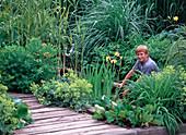 Junge am Wasserbecken mit Iris (Sumpfiris)