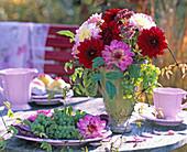 Herbststrauß in grüner Vase mit Dahlia (Dahlien) in rosa und weinrot