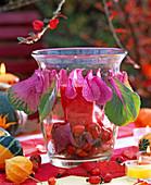 Glaswindlicht, gefüllt mit Rosa (Hagebutte), Brassica (Zierkohlblätter)