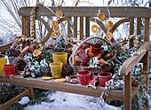 Winterliches Arrangement mit Rauhreif auf Holzbank
