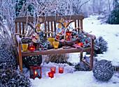Winterliches Arrangement mit Rauhreif auf Holzbank mit Lichter;