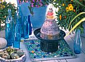 Kleiner Keramikbrunnen auf Blechtablett mit Glassteinen