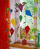 Papierdrachen und Blätter am Draht als Fensterdeko, Rosa (Hagebutten)