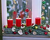 Längliches Kerzengesteck aus Zweigen, Moos und Flechten mit roten Kerzen