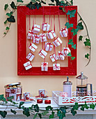 Adventskalender aus weißen Päckchen in rotem Bilderrahmen