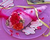Dianthus (Nelken) und Limonium (Strandflieder) in rosa Serviette