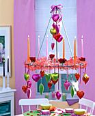 Hängende Tischdeko: Kerzenkranz mit Kerzen und Band dekoriert