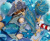Stillleben mit maritimem Weihnachtsbaumschmuck: Glaskugeln, Segelschiff, Fisch
