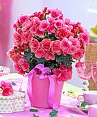 Pinkfarbene Begonia elatior (Elatior-Begonie) mit Schleife, Blätter