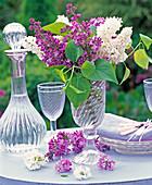 Lila und weißer Syringa (Flieder) in hoher Glasvase, Blüten, Karaffe, Weinglas