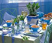 Tischdekoration mit Convallaria (Maiglöckchen), blaue Schalen