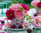 Blüten von Rosa (Rosen, hellrosa und rot) in Kaffeetasse mit Rosenmotiv