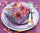 Dahlia (Dahlien), Limonium (Meerlavendel) auf lila-pinker Serviette