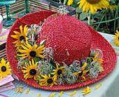 Roter Strohhut mit Kranz aus Rudbeckia (Sonnenhut), Clematis (Waldrebe)