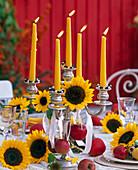 Tischdeko im Herbst mit Sonnenblumen und Äpfeln