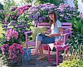 Halbschattenterrasse mit Hortensien und rosa Holzbank