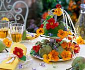 Spätsommerliche Tischdekoration mit Kapuzinerkresse und Früchten