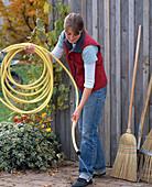Pflege von Gartengeräten: Frau läßt Wasser aus Gartenschlauch