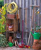 Stillleben mit Gartengeräten: Gartenschlauch, Besen, Spaten, Grabgabel