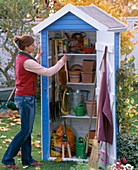 Frau hängt Besen in kleines Gerätehaus mit Töpfen und Gartengeräten