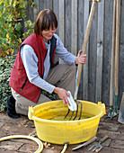 Frau reinigt Grabgabel mit Bürste und Wasser