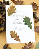 'Einladung zum Herbstfest' dekoriert mit Herbstlaub von Quercus (Eiche)