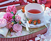 Bunch of pink rosa (rose, rosehips) on rolled napkin, teacup
