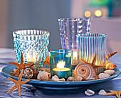 Windlichter in türkisen Gläsern mit Seesternen, Schnecken, Muscheln auf