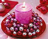 Kerzenkranz aus kleinen Weihnachtsbaumkugeln mit pinkfarbener Stumpenkerze