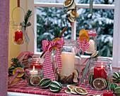 Kerzen in Einmachgläsern, gefüllt und dekoriert mit getrockneten Scheiben