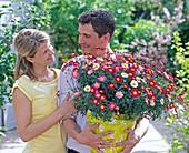 Junges Paar mit Argyranthemum 'Daisy Crazy'