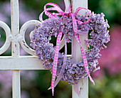 Kranz aus hellila Syringa (Flieder) mit rosa Band an weißen Metallzaun gebunden