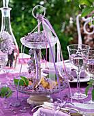 Tischdekoration mit Syringa (Flieder) und Kristallglas