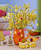 Strauß aus Forsythia (Goldglöckchen) in oranger Vase geschmückt