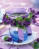 Kranz aus Viola odorata (Duftveilchen) an Kerzenglas auf Unterteller
