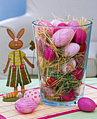 Ausgeblasene rosa Ostereier in Glasvase mit Stroh, Bambusuntersetzer, Hase