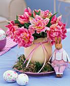 Tulipa (Tulpen) in Eiervase auf Kranz aus Moos, Buxus (Buchs) und Stroh