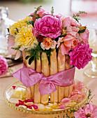 Gesteck aus Rosa (Rosen) und Asparagus (Spargel) auf Glasteller