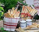 White asparagus (asparagus) in metal basket, kitchen towel