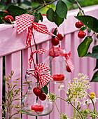Windlichter mit Prunus (Kirschen) mit karierten Bändern an Zaun