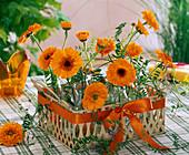 Gesteck aus Calendula (Ringelblumen) und Vicia (Vogelwicken) in flachem Korb