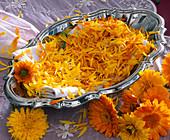Blütenblätter von Calendula (Ringelblumen) auf Tuch in silberner Schale