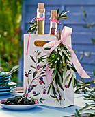 Flaschen mit Kräuter - Ölen in Papiertüte mit Olea (Oliven - Zweig) und Oliven