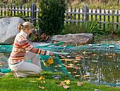 Junge Frau deckt Teich zum Schutz vor Laub mit Netz ab