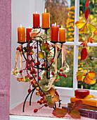 Kerzenhalter mit Hagebutten, Malus (Zieräpfeln), Clematis (Waldrebe)